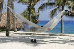Asleep on the beach. Sleeping on the beach in a hammock with shoes resting on the sand stock photography