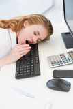 Asleep businesswoman yawning on keyboard at office Stock Photography