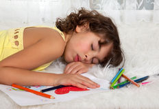 Asleep on a drawing. Little girl fallen asleep on her drawing for mother's day stock image
