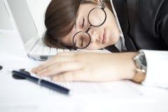 Asleep girl on the keyboard. Tired woman is sleeping on the table Stock Photography