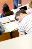 Asleep male student during an university lesson. In an auditorium Royalty Free Stock Images
