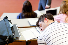 Asleep male student during an university lesson. In an auditorium Stock Photography