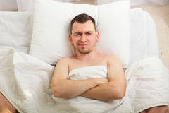 Asleep man lying in bed. Asleep man with beard lying on white pillow in bed and looking in a ceiling. Tired man under blanket at the morning. Waking up problems Royalty Free Stock Photo