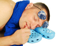 Asleep man, plimsolls, towel and antisun glasses Stock Photography