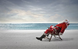 Asleep at the seaside. Santa Claus fallen asleep on a beach chair at the seaside Stock Photography
