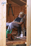 Asleep in shed. Man sitting in deckchair falling asleep in the shed while reading book royalty free stock images