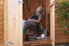 Asleep in shed. Man sitting in deckchair falling asleep in the shed while reading book stock photography