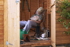 Asleep in shed. Man sitting in deckchair falling asleep in the shed royalty free stock photography