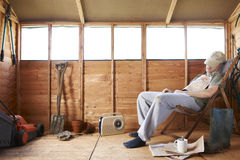 Asleep in shed. Man sitting in deckchair falling asleep in the shed royalty free stock image