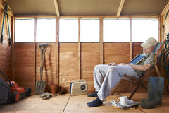 Asleep in shed. Man sitting in deckchair falling asleep in the shed royalty free stock photos