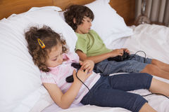 Asleep siblings while playing video games in bedroom Stock Photography