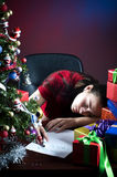 Asleep with wish list to Santa. Sleeping without finishing the wish list to Santa at the office Royalty Free Stock Image