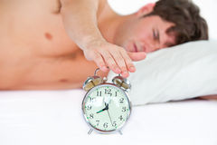 Asleep young man stopping his ringing alarm clock Royalty Free Stock Image