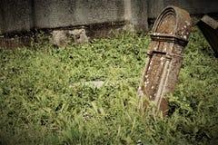 Asloped tombstone on the graveyard. Asloped tombstone on the abandoned graveyard Royalty Free Stock Images