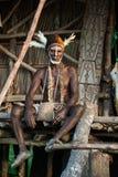Asmat avec une peinture traditionnelle sur un visage, le chapeau du cuscus et les plumes de cacatoès Image stock
