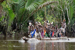 Asmat men paddling in their dugout canoe. Canoe war ceremony of Asmat people. Headhunters of a tribe of Asmat show traditional and national customs, dresses Royalty Free Stock Photography