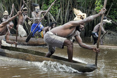 Asmat men paddling in their dugout canoe Stock Photos