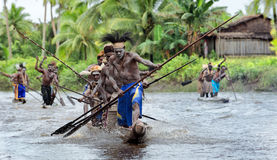 Asmat men paddling in their dugout canoe Royalty Free Stock Images