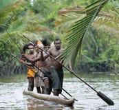 Asmat män som paddlar i deras dugoutkanot Arkivbild