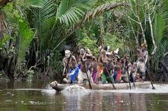 Asmat män som paddlar i deras dugoutkanot Arkivfoton