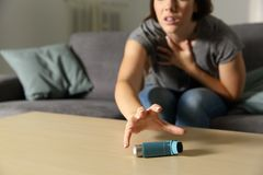 Asmathic girl catching inhaler having an asthma attack. Sitting on a couch in the living room at home stock image