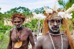 Asmats avec une peinture traditionnelle sur un visage, le chapeau du cuscus et les plumes de cacatoès J Photos stock