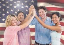 ASmilings-Freunde mit den Händen zusammen gegen amerikanische Flagge Stockfotos