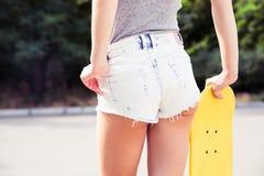 Asno femenino en pantalones cortos con los monopatines al aire libre Fotos de archivo libres de regalías