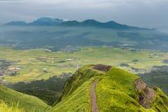 Aso-Vulkangebirgs- und -landwirtdorf von der Bergkuppe in Kumamot Lizenzfreie Stockbilder