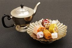 Oriental sweets in a low metal vase on a dark table Stock Photo