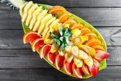 Asortowane świeże owoc na talerzu Apple, pomarańcze, ananas, grapefruitowy, banan i mennica na ciemnym tle obraz stock