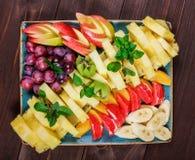 Asortowane świeże owoc na talerzu Apple, winogrona, kiwi, ananas, grapefruitowy, pomarańczowy, banan i mennica na drewnianym stol obrazy royalty free