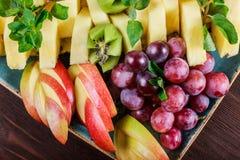 Asortowane świeże owoc na talerzu Apple, winogrona, kiwi, ananas, grapefruitowy, pomarańczowy, banan i mennica na drewnianym stol zdjęcie stock