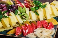 Asortowane świeże owoc na talerzu Apple, winogrona, kiwi, ananas, grapefruitowy, pomarańczowy, banan i mennica na drewnianym stol fotografia stock