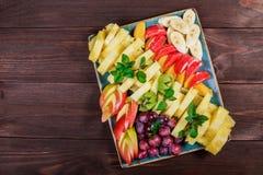 Asortowane świeże owoc na talerzu Apple, winogrona, kiwi, ananas, grapefruitowy, pomarańczowy, banan i mennica na drewnianym stol zdjęcia royalty free