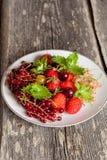 Asortowane ogrodowe jagody na talerzu na drewnianym tle Obrazy Royalty Free