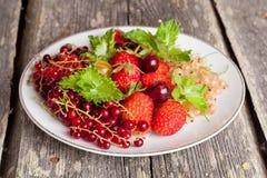Asortowane ogrodowe jagody na talerzu na drewnianym tle Zdjęcia Stock