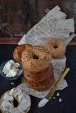 Asortowani Bagels z kremowym serem na wieśniaka stole z muzycznymi prześcieradłami obraz stock