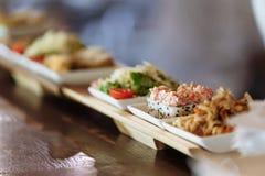 Asortowani japo?czyk?w naczynia w bia?ego kwadrata talerzach na drewnianych stojakach na tle st?? zdjęcie stock