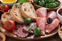 Asortowani Włoscy antipasti mięsa, oliwki i chleb - delikatesów, Obrazy Stock