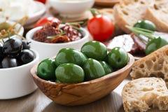 Asortowani Włoscy antipasti oliwki, zalewy i chleb -, obraz royalty free