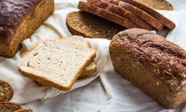 Asortowany chleb, plasterki żyto chleb na bieliźnianych tablecloths, drewniani Zdjęcia Royalty Free