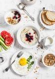 Asortyment śniadanie - oatmeal z jagodami, smażącym jajkiem, świeżymi warzywami, chałupa serem, jogurtem i jagodami, domowej robo Obrazy Stock