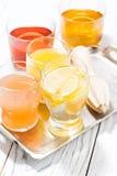 Asortyment świezi cytrusów soki w szkłach na bielu stole Zdjęcie Royalty Free