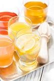 Asortyment świezi cytrusów soki w szkłach na bielu stole, ver Fotografia Royalty Free