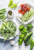 Asortyment świezi ogrodowi warzywa - asparagus, brokuły, fasole, pieprze, pomidory, ogórki, czosnek, zieleni grochy na lekcy półd Obraz Stock