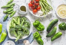 Asortyment świezi ogrodowi warzywa - asparagus, brokuły, fasole, pieprze, pomidory, ogórki, czosnek, zieleni grochy na lekcy półd zdjęcie stock