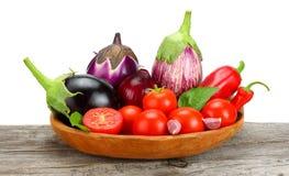 Asortyment świezi surowi warzywa na starym drewnianym stole z białym tłem Pomidor, oberżyna, cebula, chili pieprz fotografia stock
