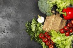 Asortyment świezi warzywa pieprzy, czereśniowi pomidory, cebule, czosnek, brokuły, sałata na ciemnym tle Obraz Stock