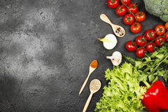 Asortyment świezi warzywa pieprzy, czereśniowi pomidory, cebule, czosnek, brokuły, sałata na ciemnym tle i różnorodna pikantność, Obraz Royalty Free